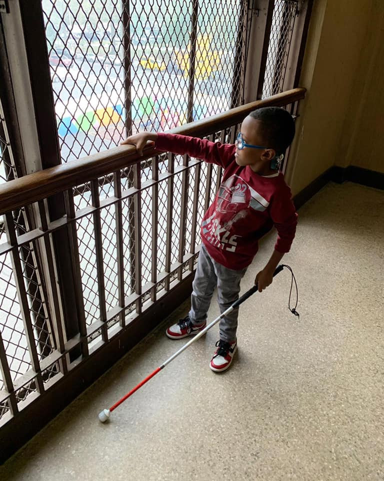 A male elementary student wearing blue glasses uses a white cane in his left hand while his right hand holds on the top of a safety gate next to a window. He is looking out the window.