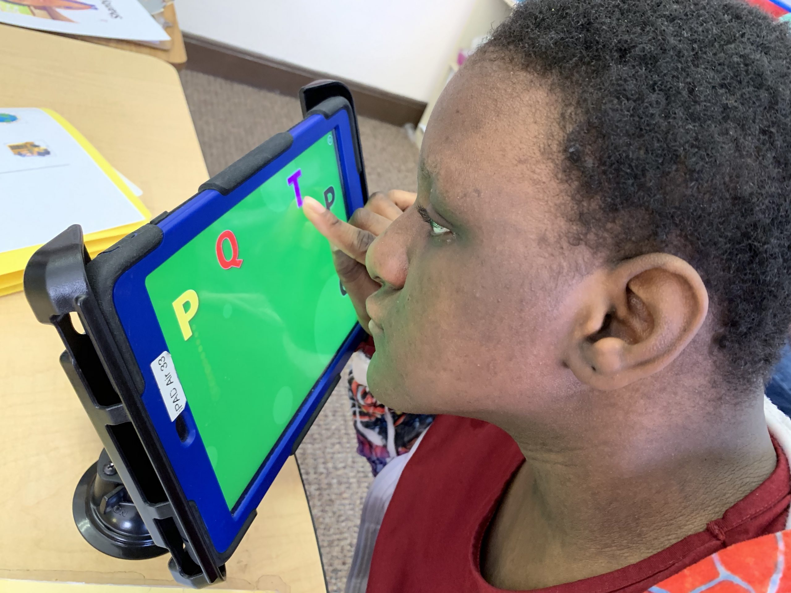 A middle school female student is using an iPad. She is matching the letters in a game.