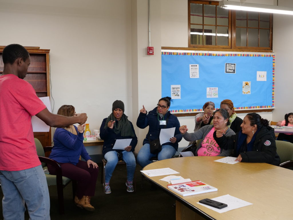 In the Family Education room, a male Deaf instructor is standing in front of a group teaching American Sign Language. The family members are copying his signs. A child is seated in the back of the room.