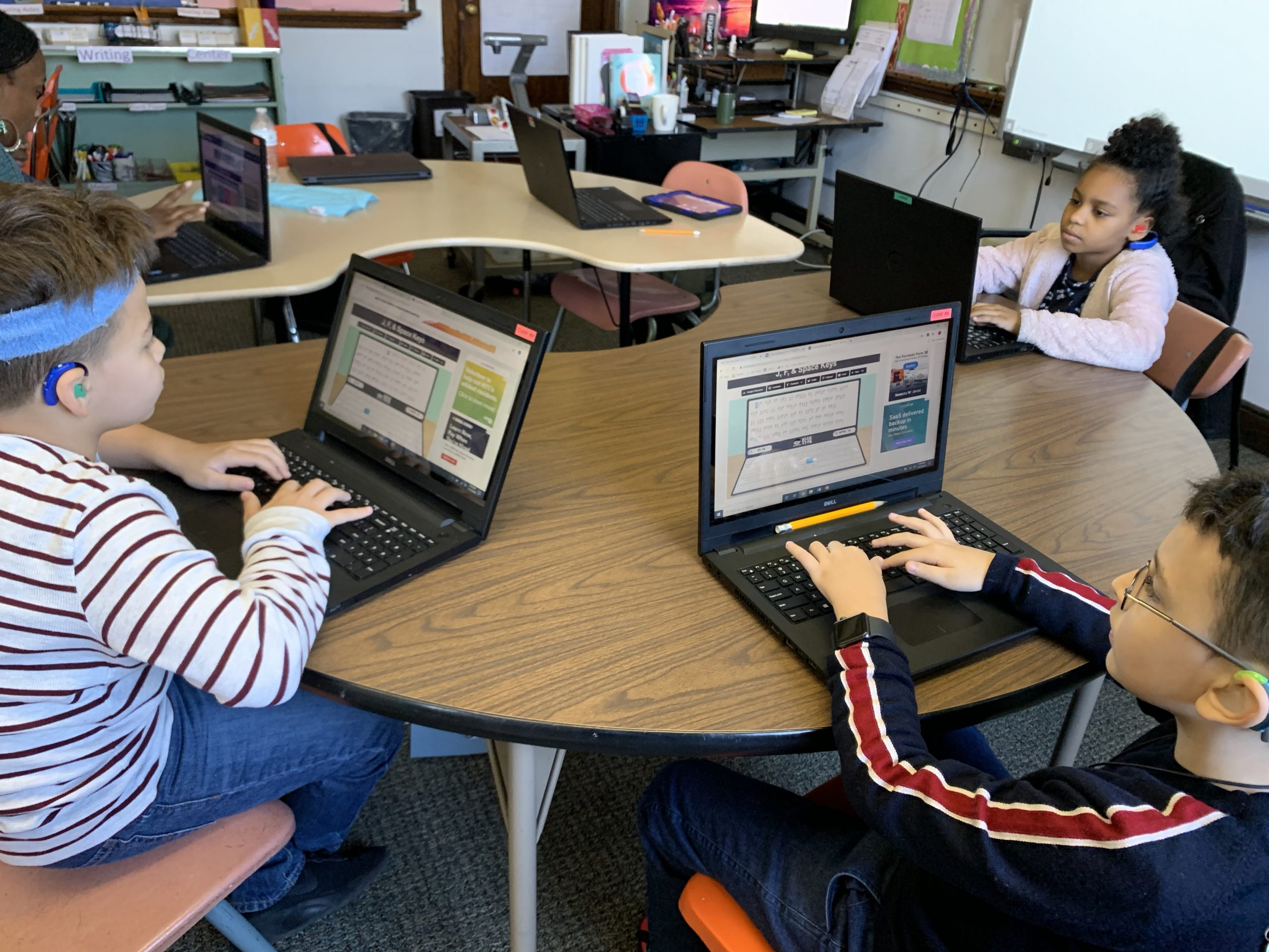 A female teacher and three 4th grade students are typing on their laptops in a classroom. They are focused on their own work as they sit at kidney bean shaped tables working independently.