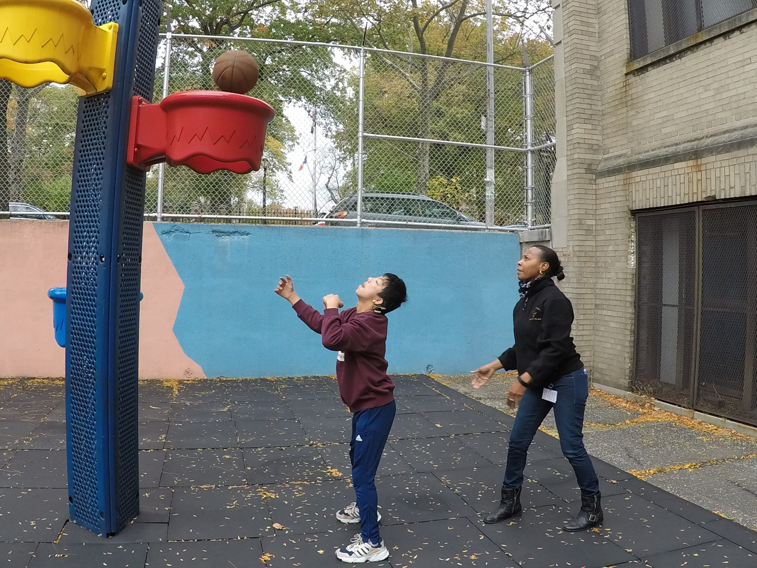 A male middle school student is playing basketball with the female occupational therapist outside on the playground. Both their eyes are on the ball as it is about to go through the hoop.