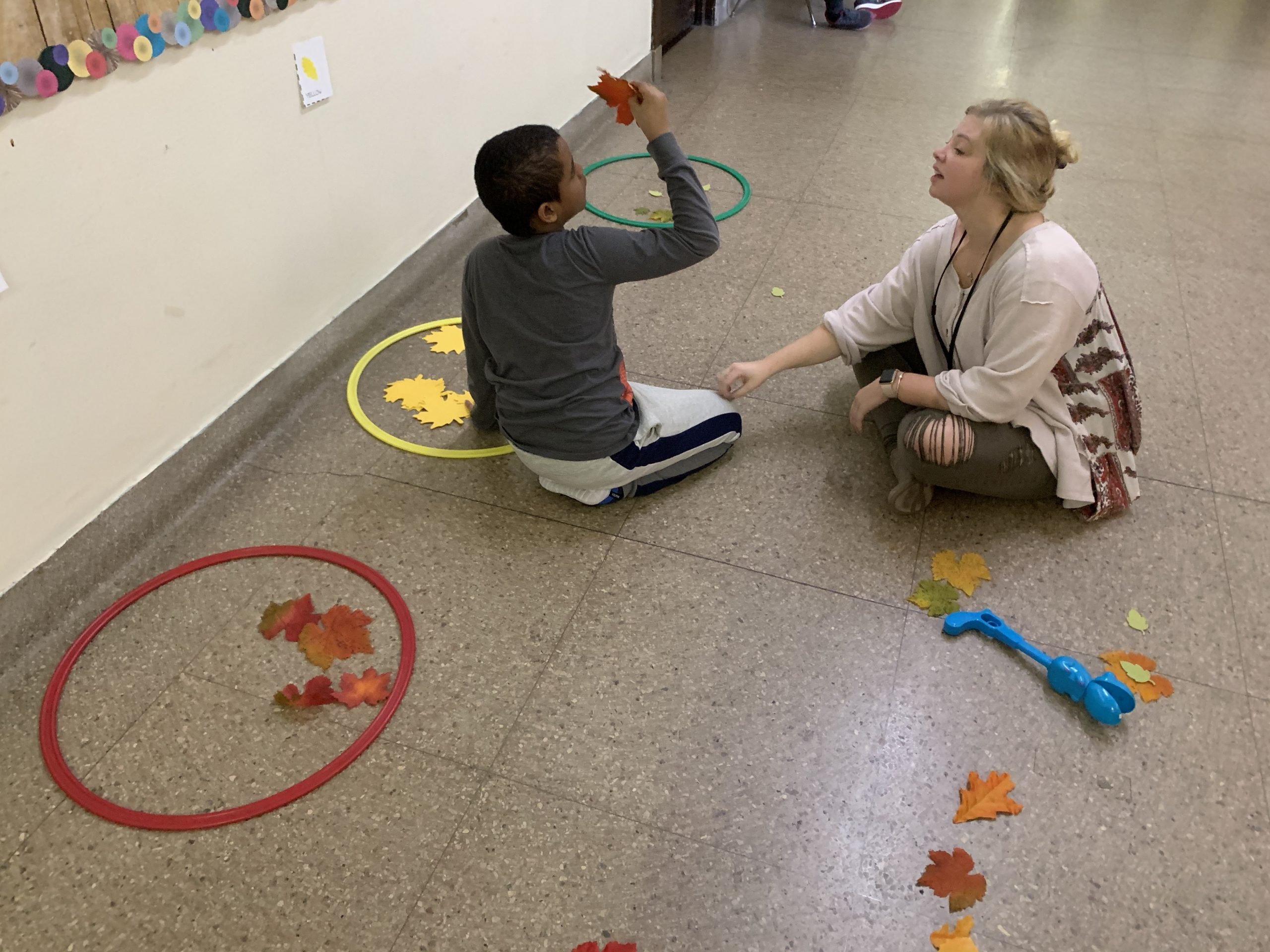 In a hallway, a middle school male student is kneeling on the floor by three circles of different colors (red, yellow, green), leaves and light blue hand grabber while the occupational therapist sits next to him. They appear to be doing a sorting activity. The student holds an orange leaf and is looking at it while the OT is tapping the student to gain his attention.