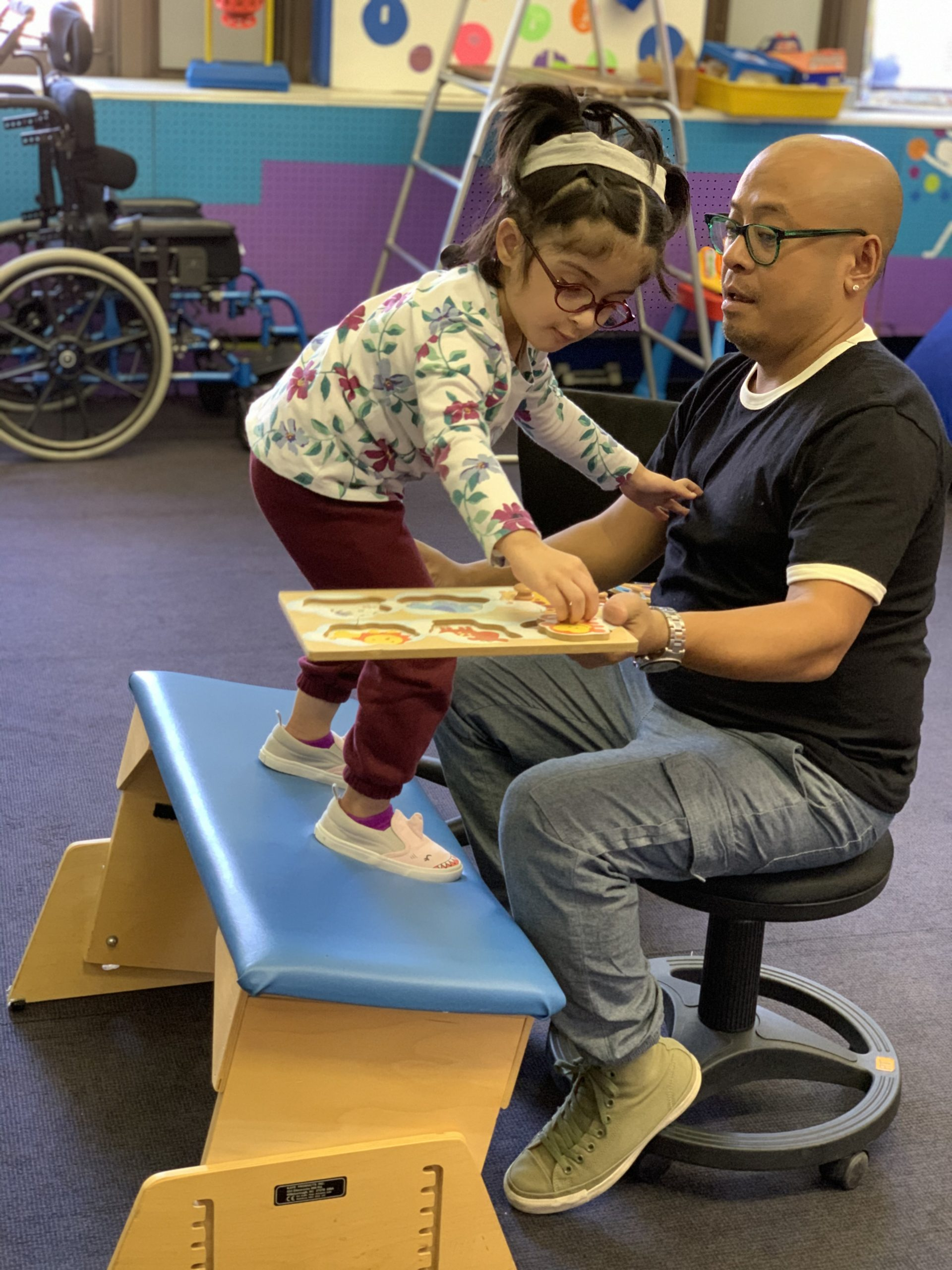A female preschool student is balancing on a rocking therapy bench as she works on a puzzle with knobs. A male physical therapist is sitting in front of the student and is holding the board of the puzzle.