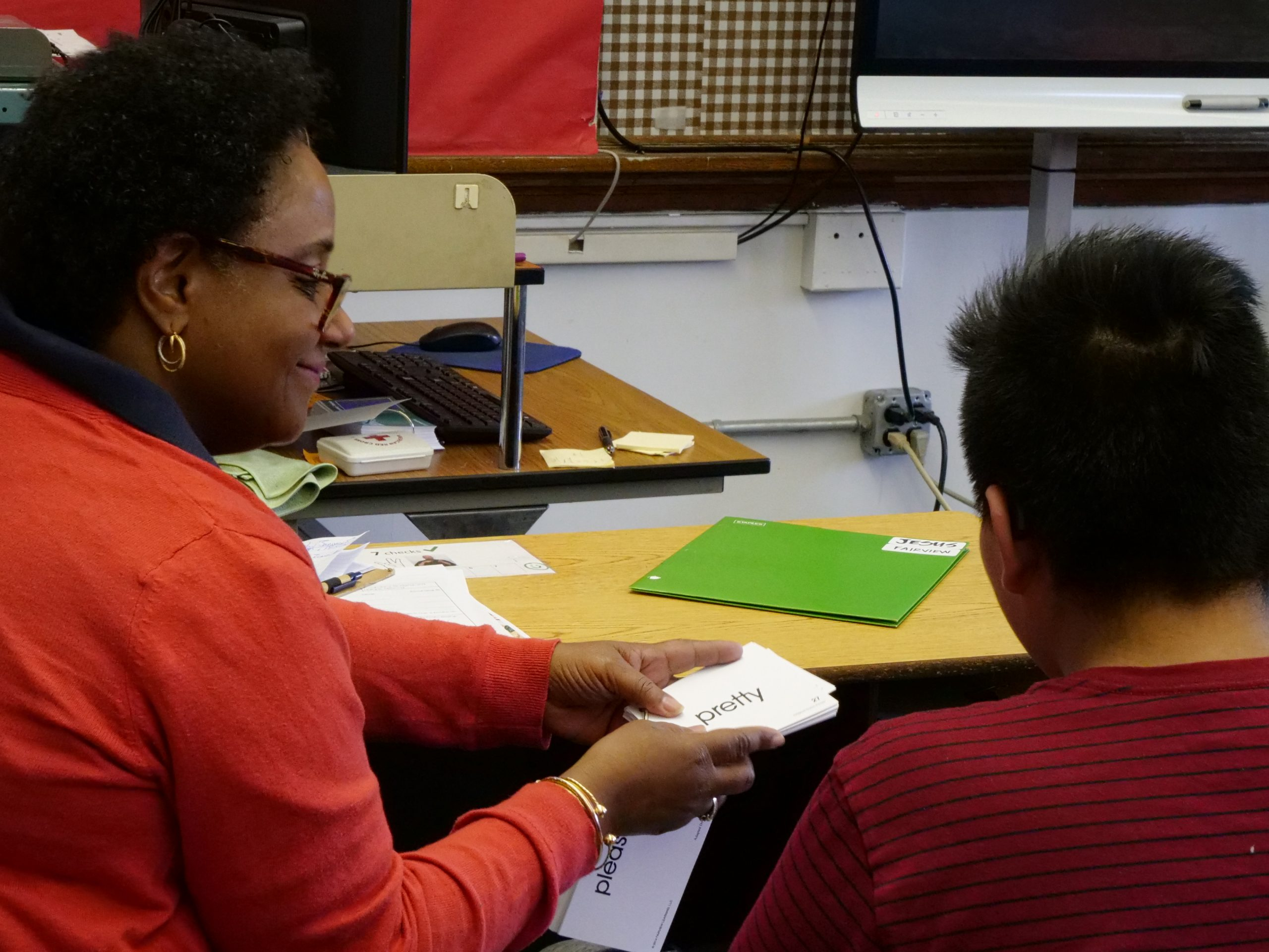 """A female speech language pathologist holding a stack of sight word flashcards with both of her hands during a Push-In session. She is sitting next to a male middle school male student to the side of a classroom. The male student is looking at the flashcard, it reads """"pretty."""""""