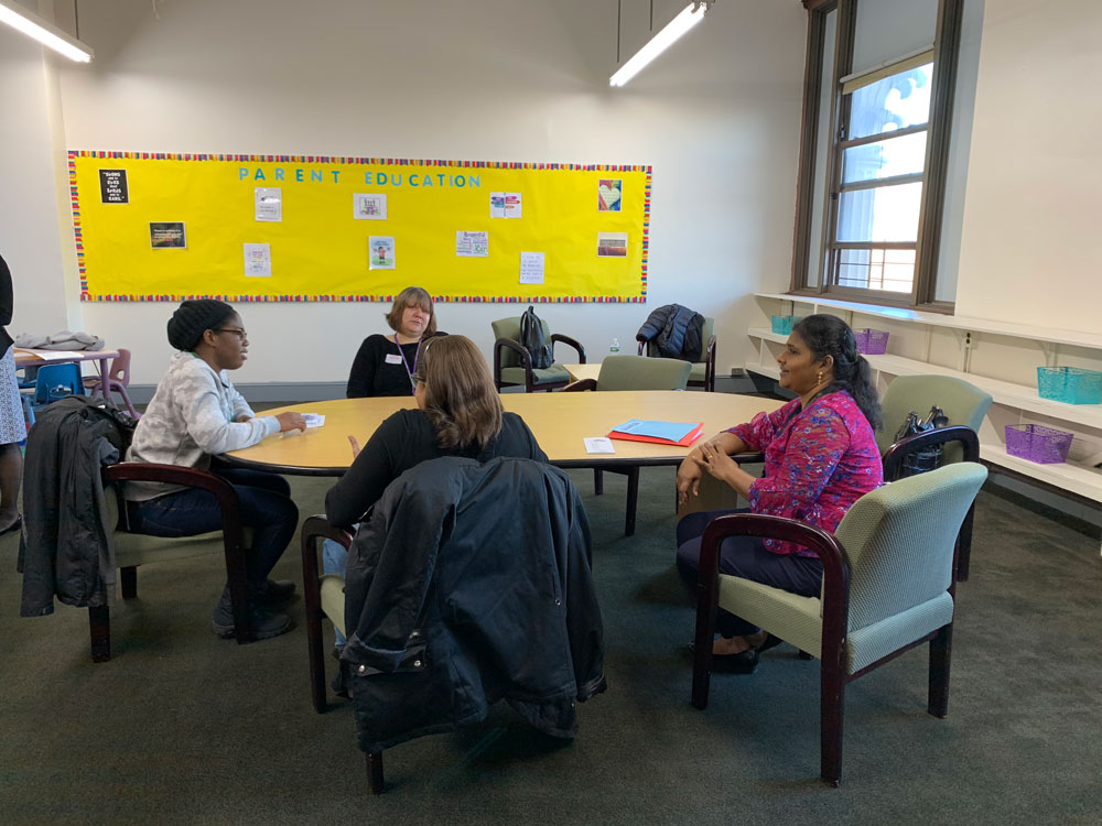 """In the Family Education room, a female social worker is sitting with a small group of mothers at an oval shaped table. In the background, there is a bulletin board with yellow paper and green letter stencils that read """"Parent Education."""""""